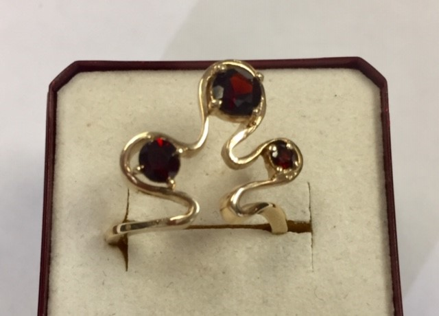 Lot 22 - A stylised Bernard Instone 9ct gold and garnets ring, wave form to the top with three claw set round