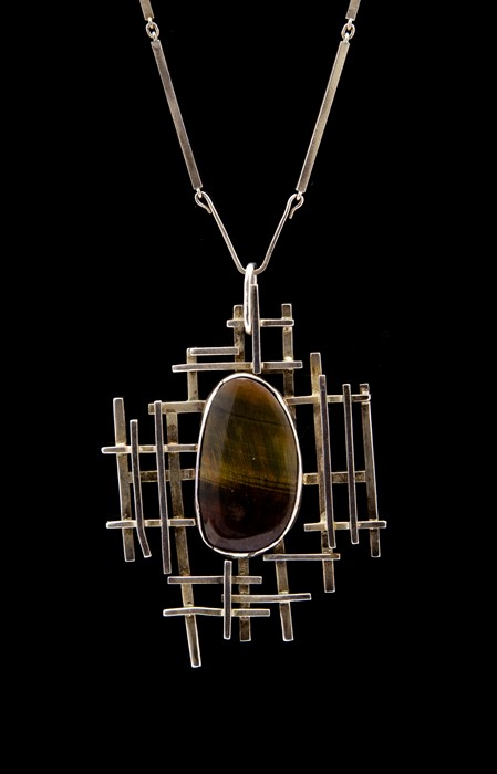 Lot 11 - A modernist silver and tiger's eye pendant necklace, the oval cabachon stone approx 2.1cm x 3.7cm,