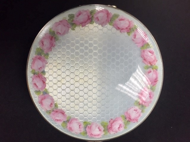 Lot 7 - A large round powder box - pale blue enamel to top and sides - border of pink enamel roses to lid.
