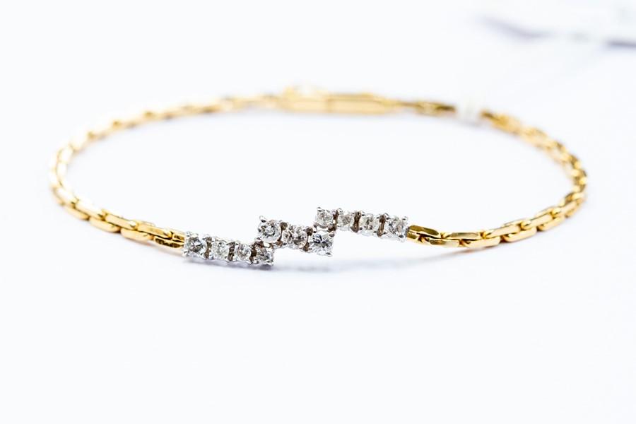 Lot 243 - A diamond set bracelet, comprising three off-set rows of claw set diamonds, the centre set with
