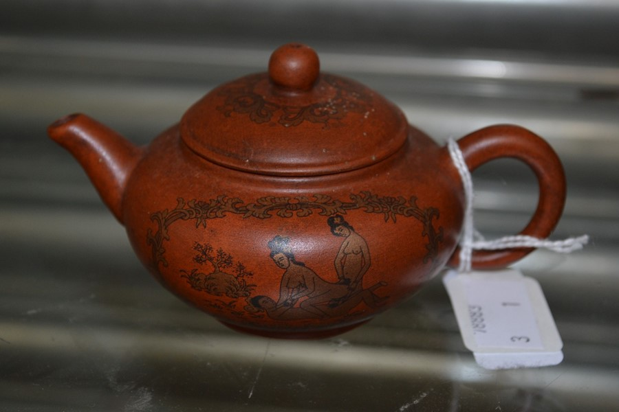 Lot 2243 - A clay Chinese teapot depicting erotic scenes.