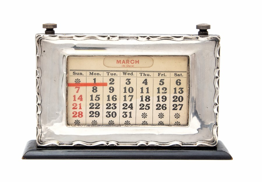 Lot 42 - A George V silver mounted desk calendar,with articulated date adjust on a polished wooden stand, by