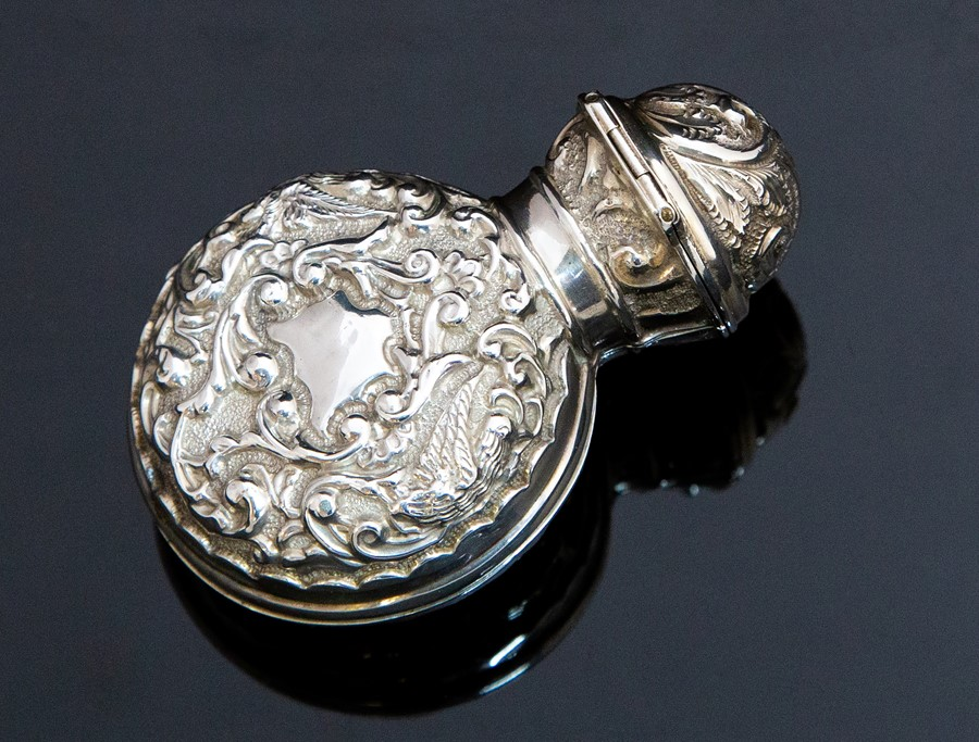 Lot 25 - An Edwardian silver cased green perfume bottle and stopper, the silver articulated case opens to