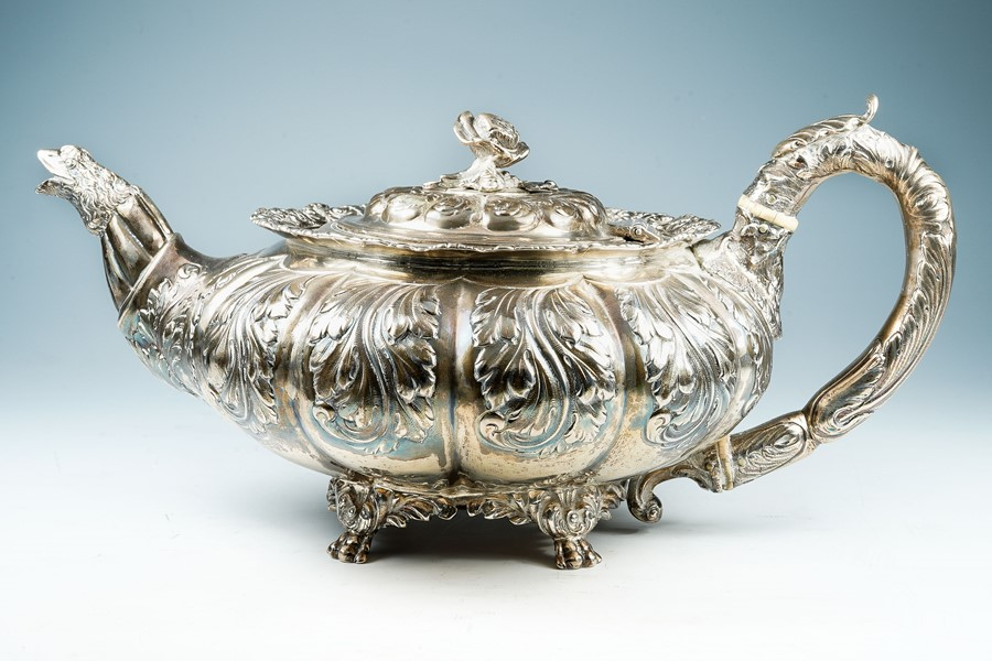 Lot 43 - A George IV melon shaped silver teapot, the body with fluted section profusely chased with