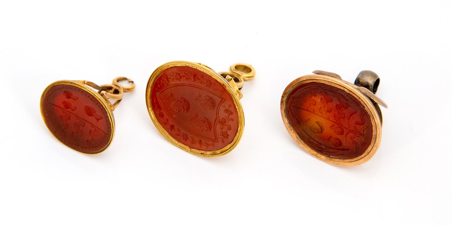 Lot 51 - Three 19th century yellow metal seal fobs, each set with carnelian carved with crests depicting