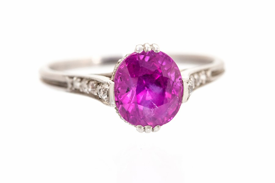 Lot 57 - An Art Deco ruby single-stone ring with diamond set shoulders and mount, the oval mixed-cut ruby