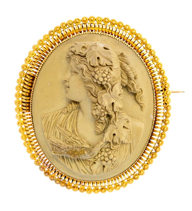 Lot 56 - A large 19th century oval lava cameo brooch, carved depicting a bacchante with grapevine and bird,