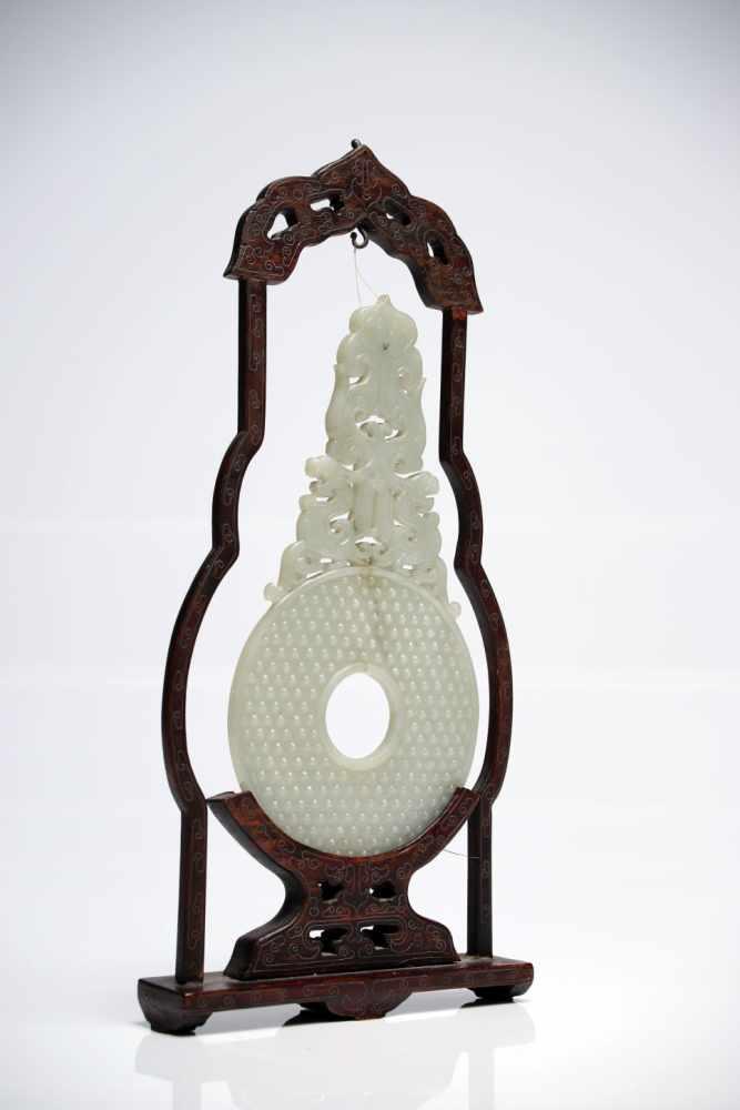 Lot 28 - Chinese Jade Bi in wood frameWhite JadeChinaH: 30 cm This delicately carved jade bi comes in a