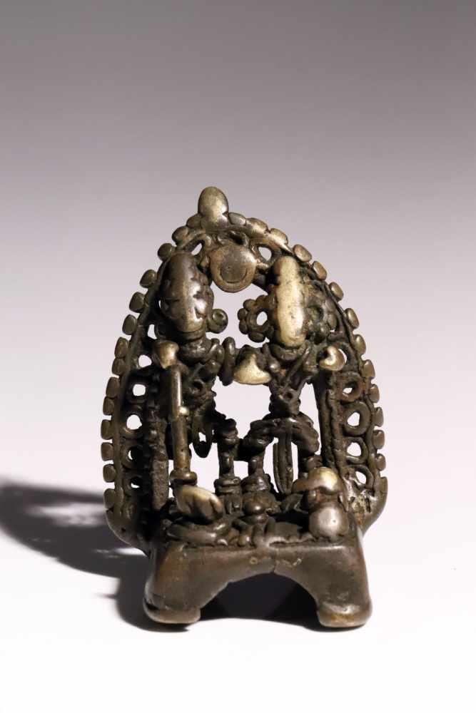 Lot 57 - House ShrineBronzeIndia16th ctH: 8 cmA small house shrine with two deities before an aureole.S894