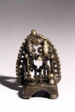 Lot 57 - House ShrineBronzeIndia16th ctH: 8 cmA small house shrine with two deities before an aureole.S894