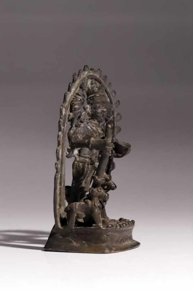 Lot 55 - VishnuBronzeIndia18th ctH: 11 cmA four-armed Vishnu before an aureola and holding attributes: a