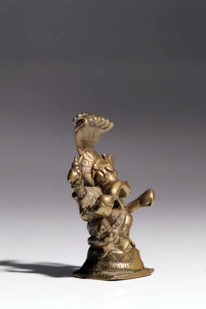 Lot 56 - GaneshaBronzeIndia17th ctH: 7 cmA four-armed Ganesha god sitting wide-legged on a conic base. He