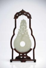 Lot 28 - Chinese Jade Bi in wood frameWhite JadeChinaH: 30 cm This delicately carved jade bi comes in a