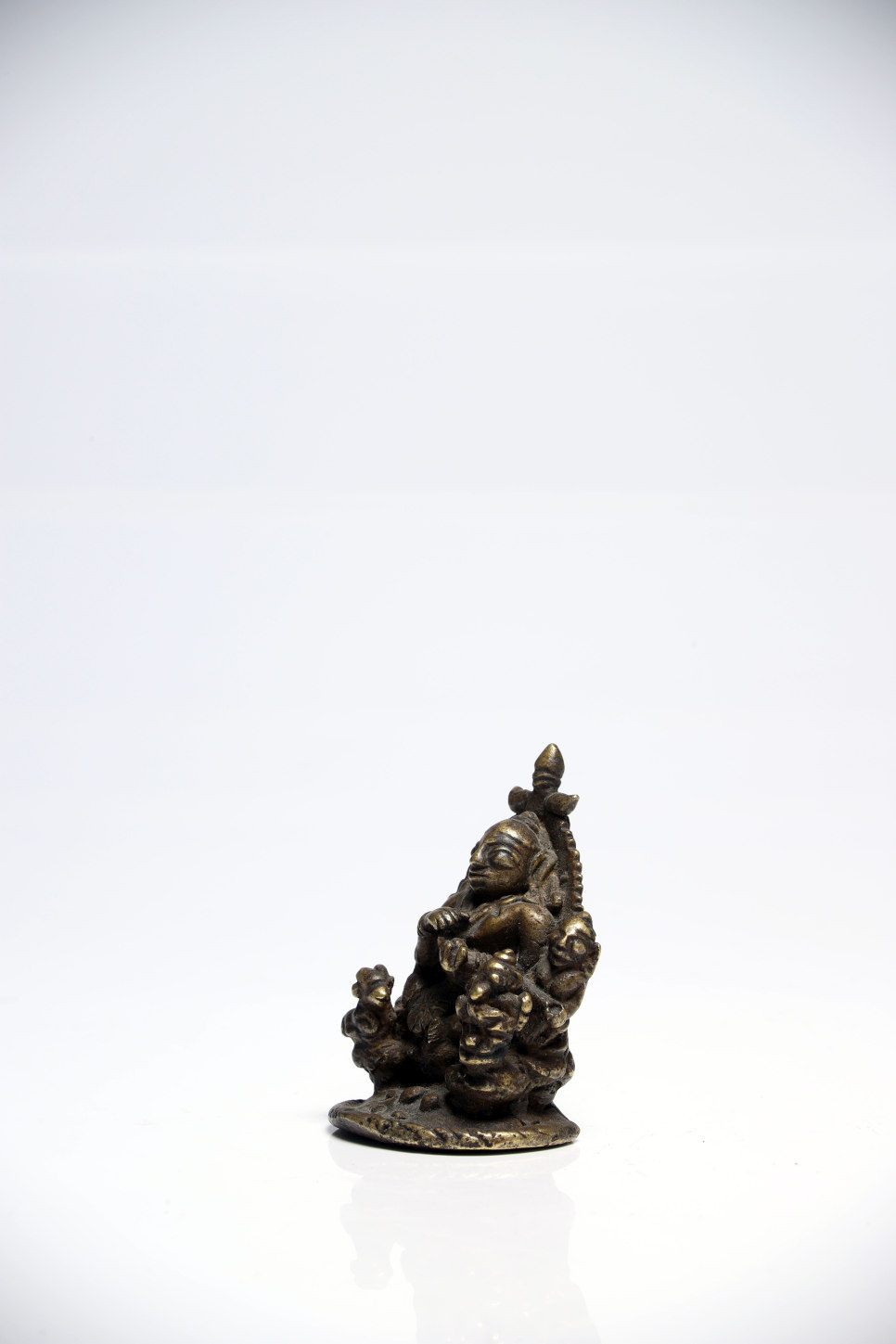 Lot 48 - Shiva and familyBronzeIndia18th ctH: 6,5 cmA small statue of a seated Shiva surrounded by his