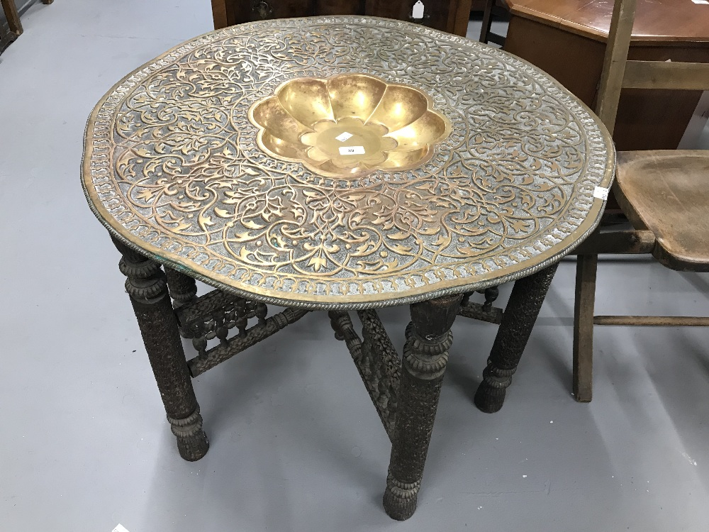 Lot 39 - Early 20th cent. Anglo Indian beaten brass table with carved folding base. Diameter 36ins.