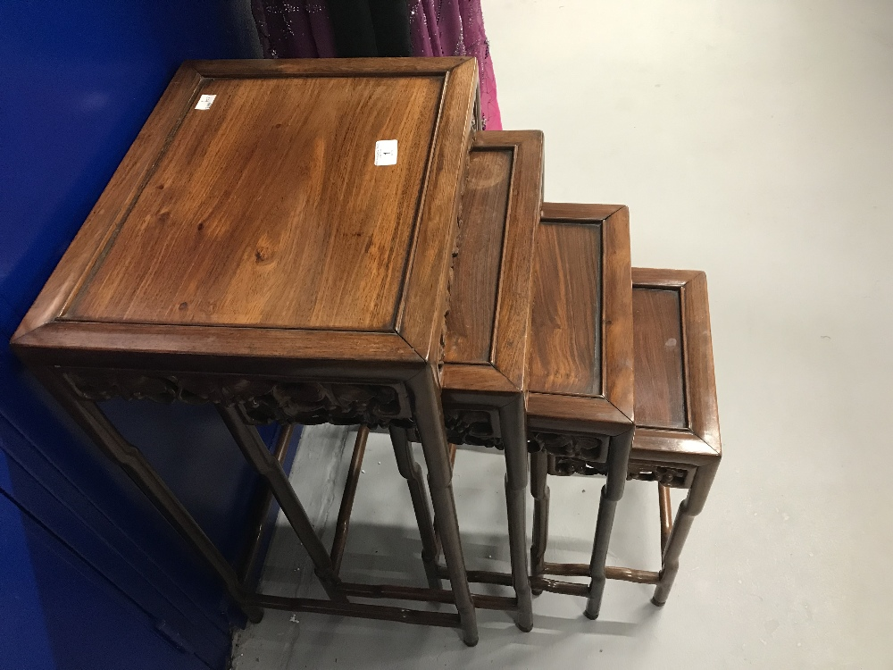 Lot 1 - 20th cent. Chinese hardwood furniture. Nest of four tables with heavily carved decoration made by C.