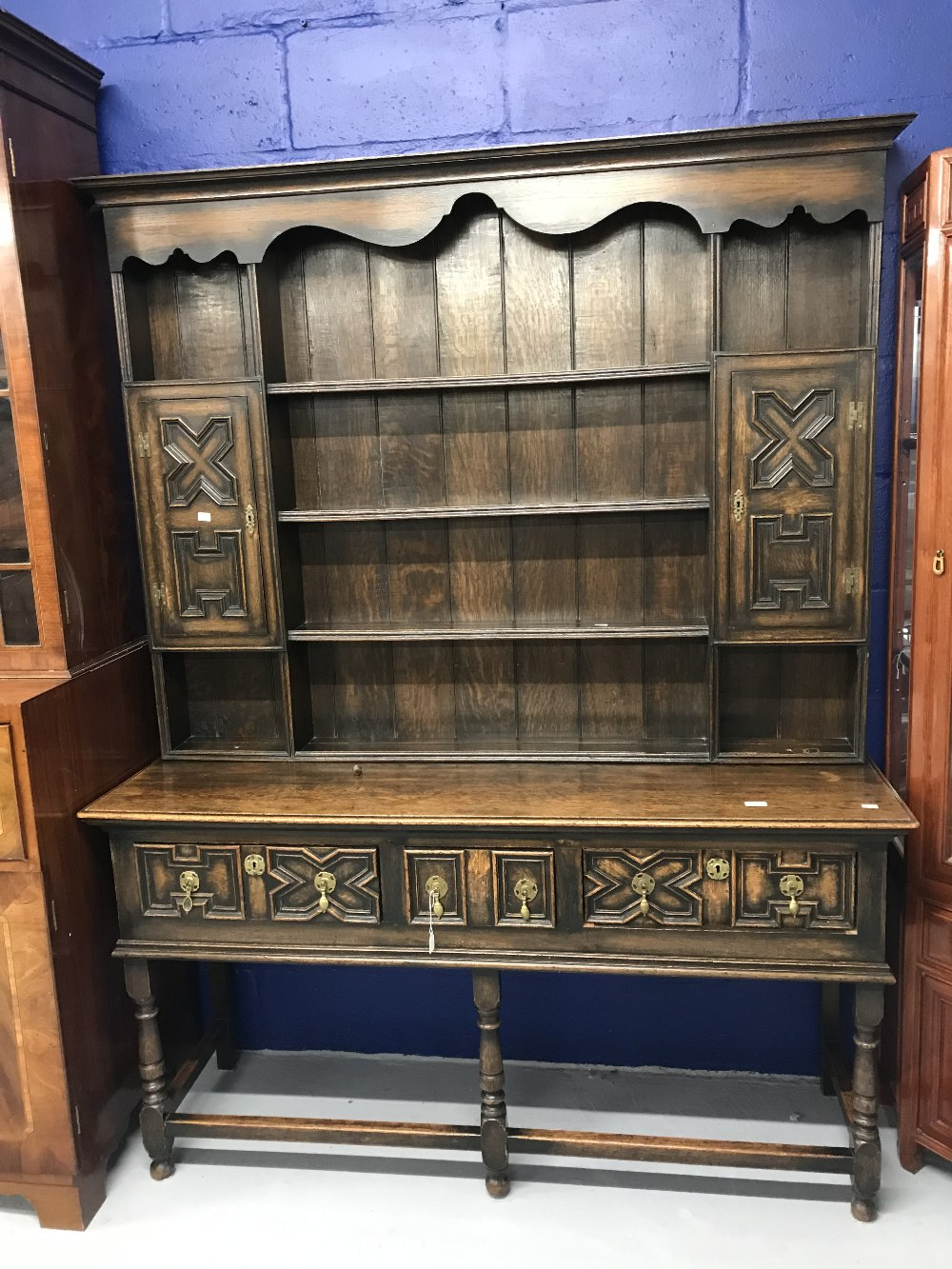 Lot 5 - 1930s, 17th cent. style, oak dresser with geometric mouldings and brass pear drop handles on