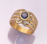 18 kt gold ring with sapphire and diamonds ,YG 750/000, centered with round bevelled sapphire
