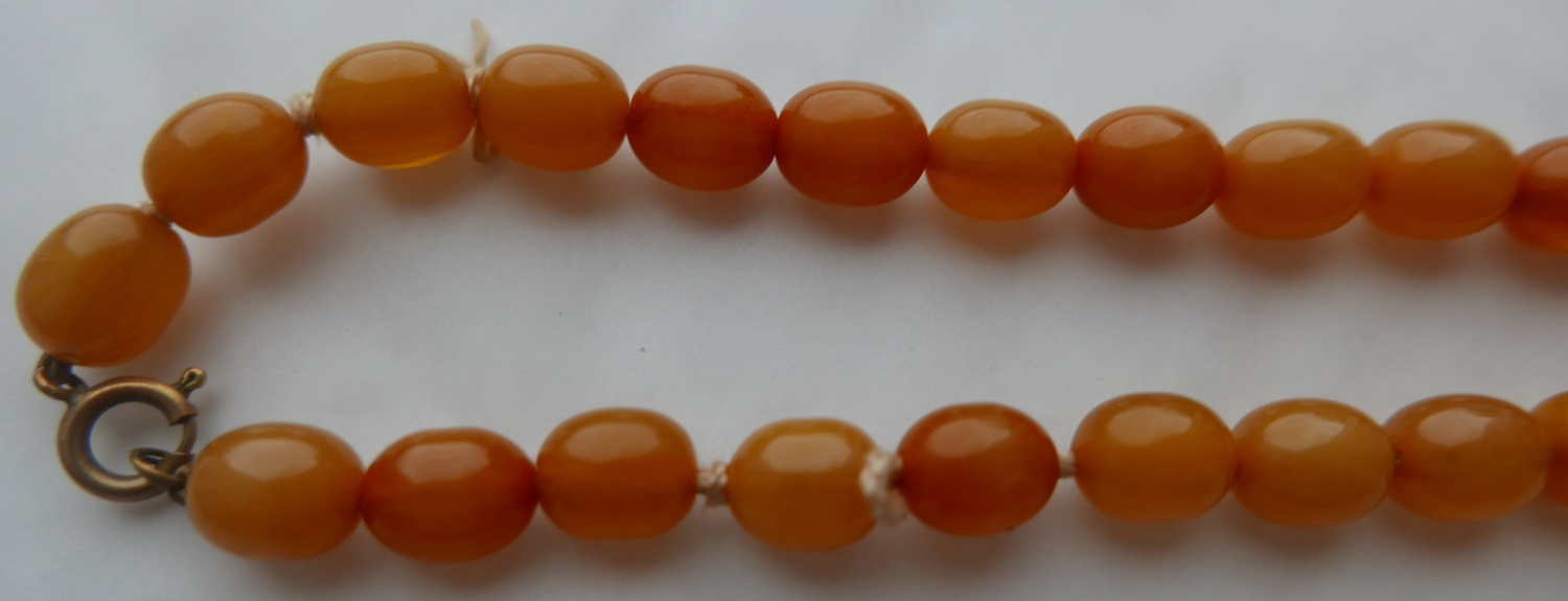 "Lot 49 - String of Egg Yolk Amber Beads - 92 grams - string 25"" (63cm) long largest bead approx 27x22mm."