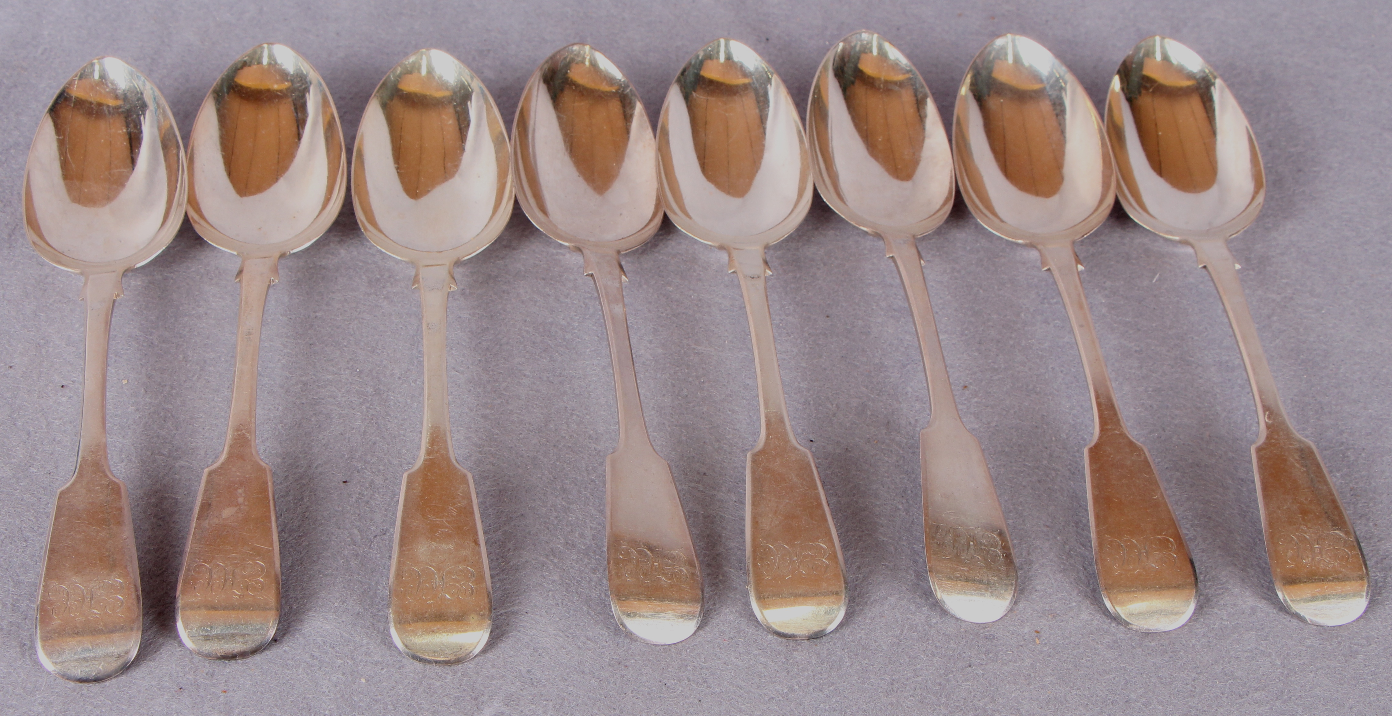 Lot 39 - A set of eight William IV silver fiddle pattern table spoons, engraved cursive initials,