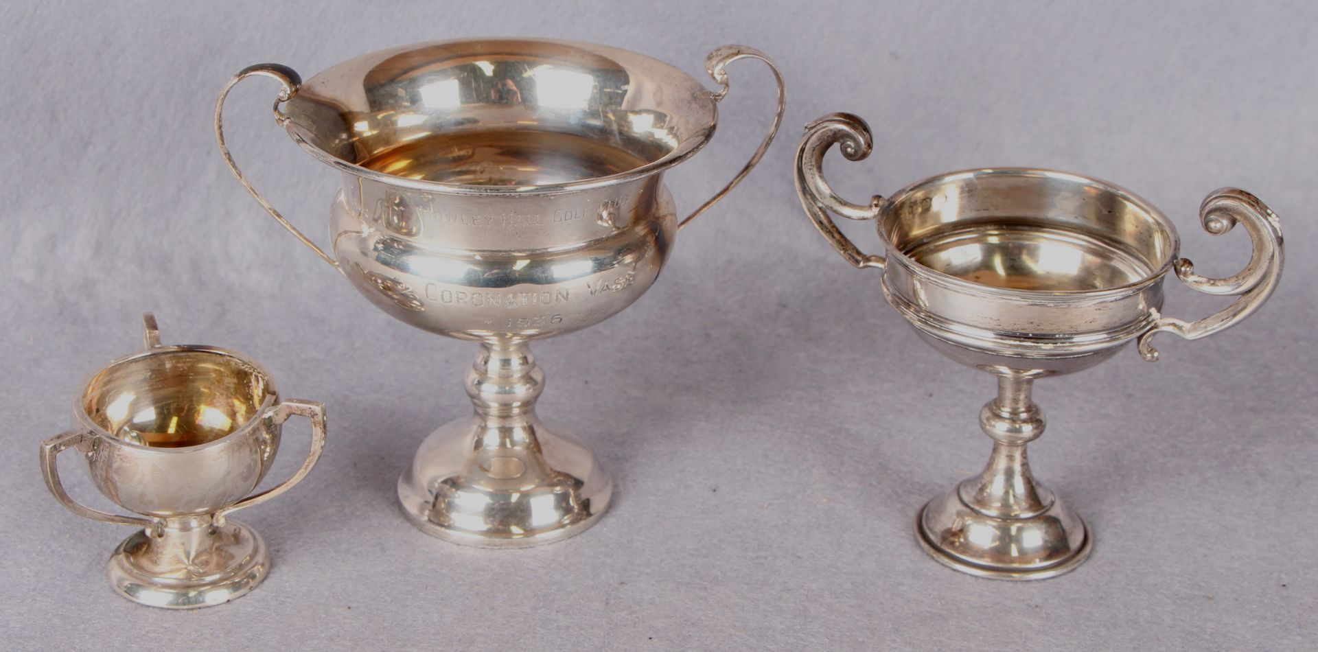 Lot 53 - Two small two handled trophy cups, each on a pedestal base,
