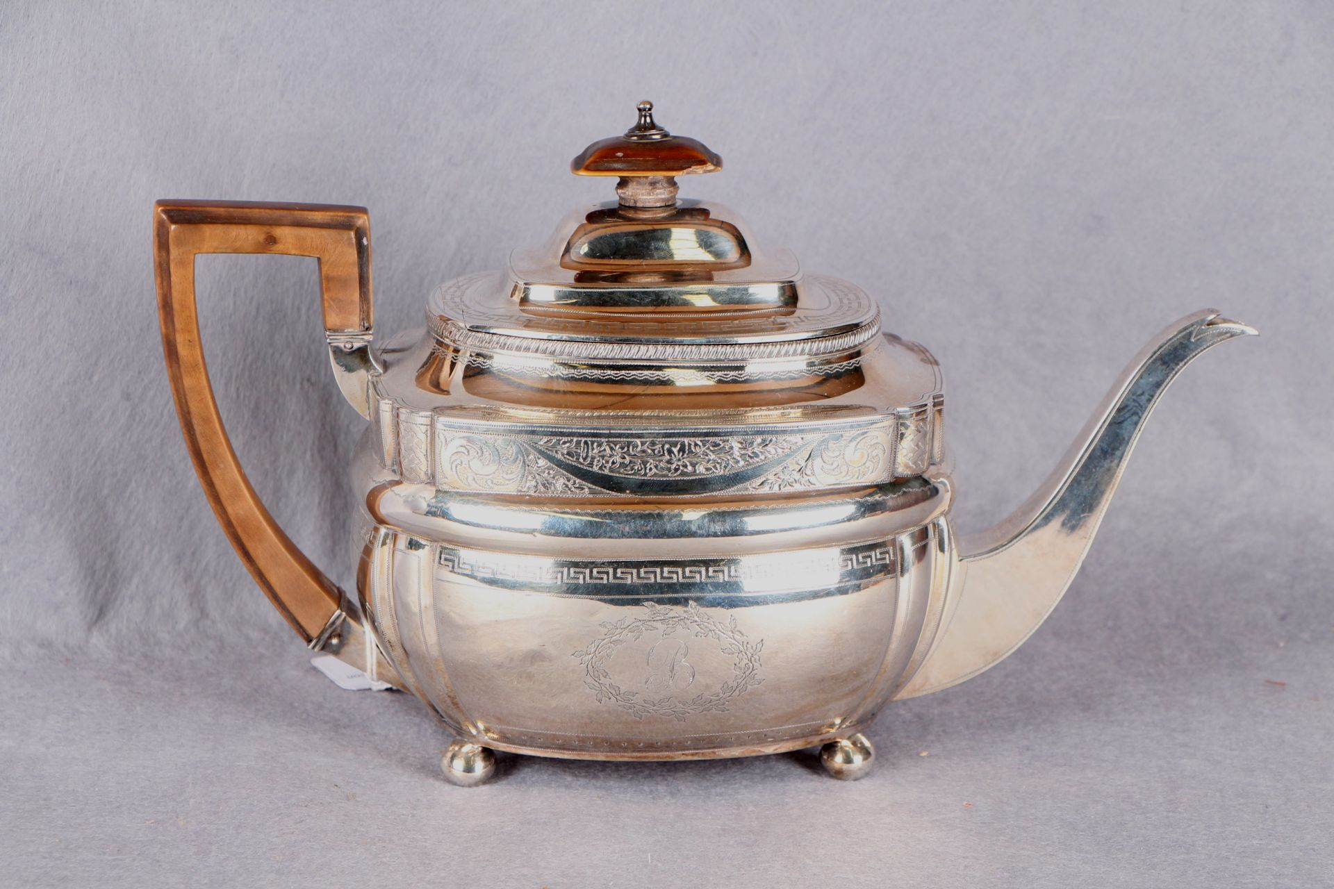 """Lot 28 - A George III silver teapot of shaped oval form, bright cut and initialled """"B"""", four ball feet,"""