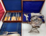 Lot 17 - A plated spirit kettle on stand and two part canteens of plated cutlery