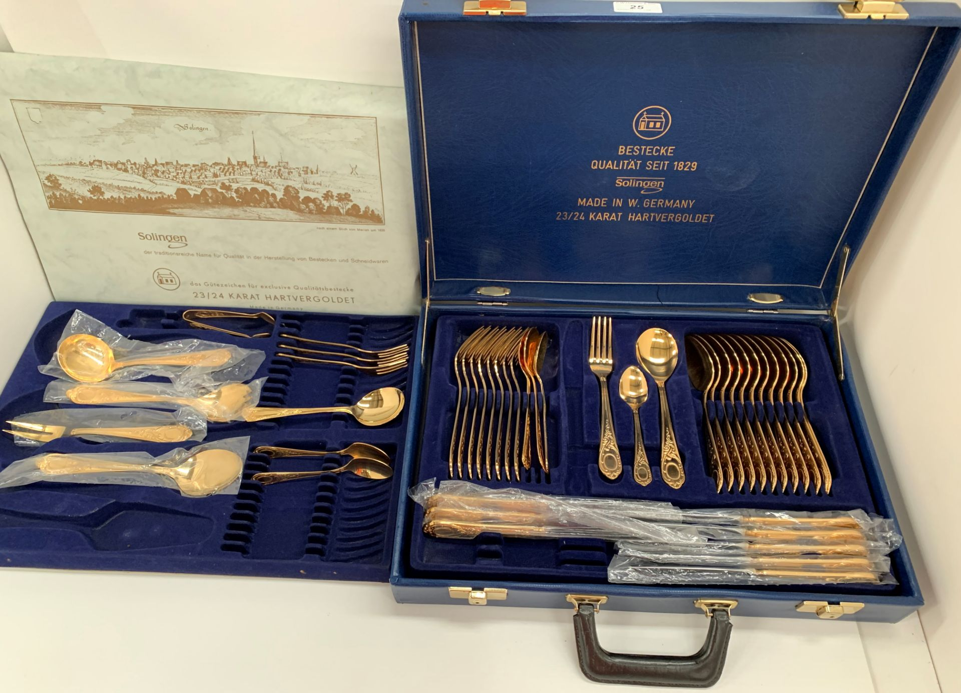 Lot 25 - A Solingen 24 carat gold plated part canteen of table cutlery in a blue leatherette case