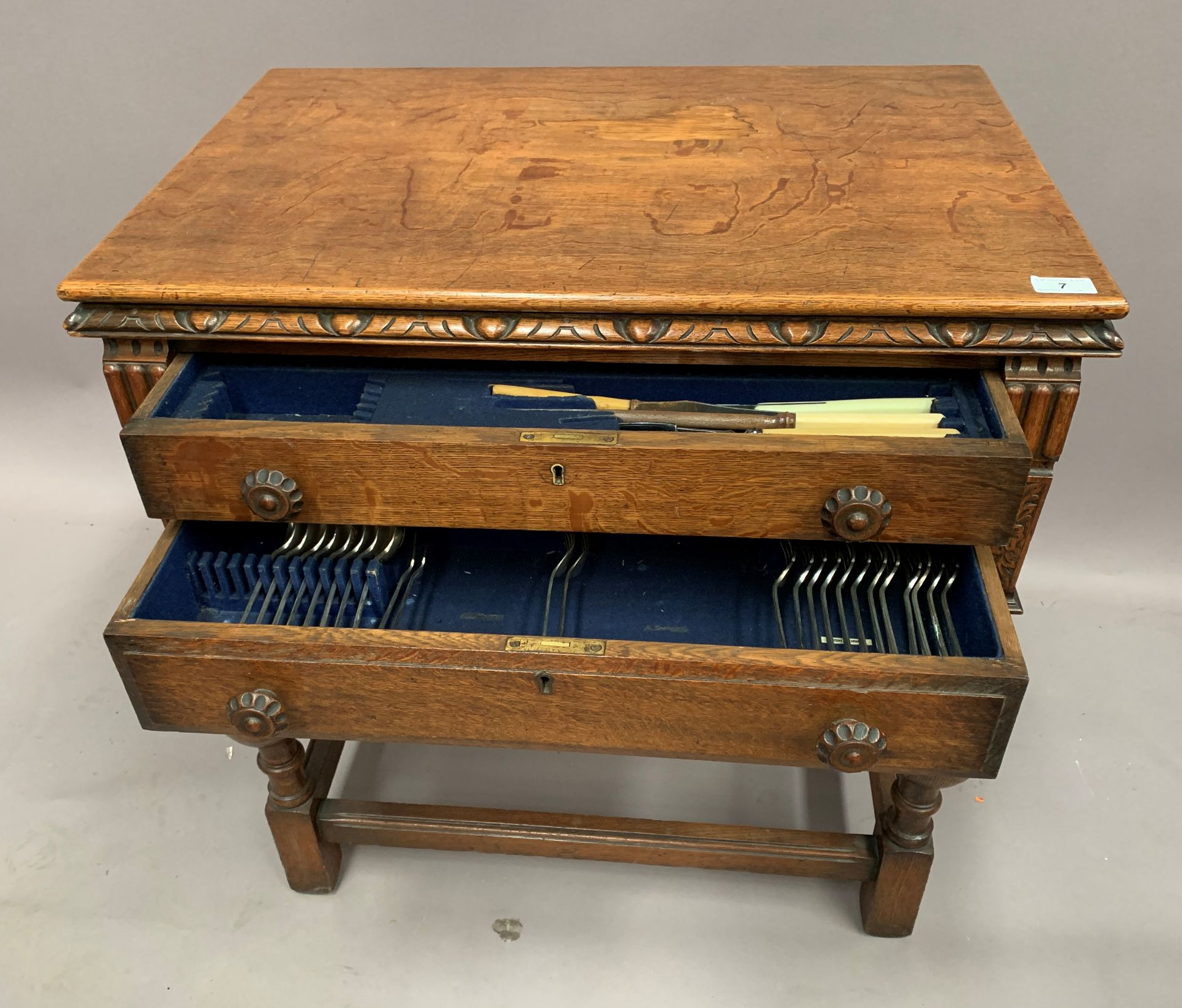 Lot 7 - A part suite of table cutlery in an oak two drawer table canteen table,