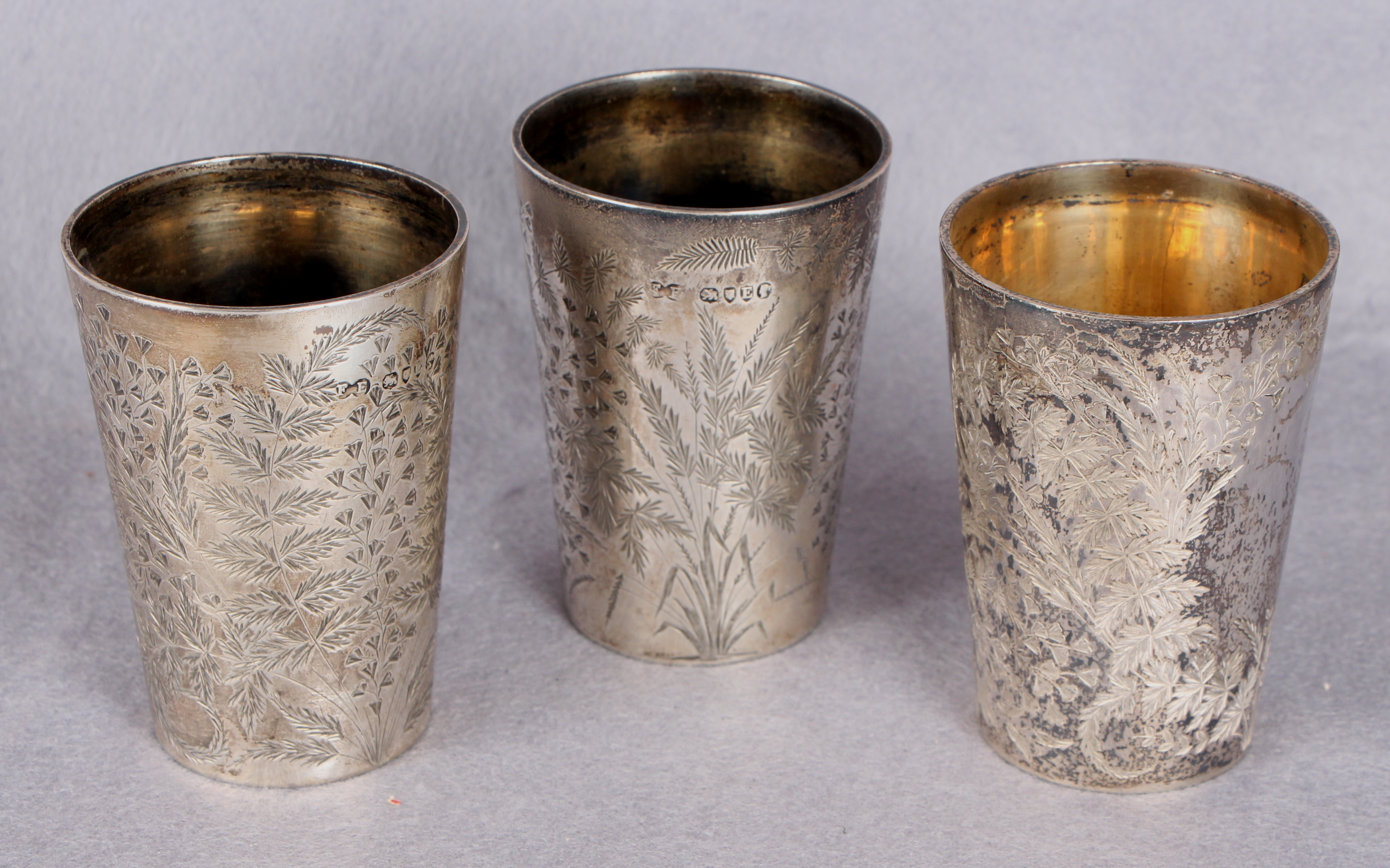 Lot 29 - Three Victorian fern-engraved silver beakers of tapering circular form,
