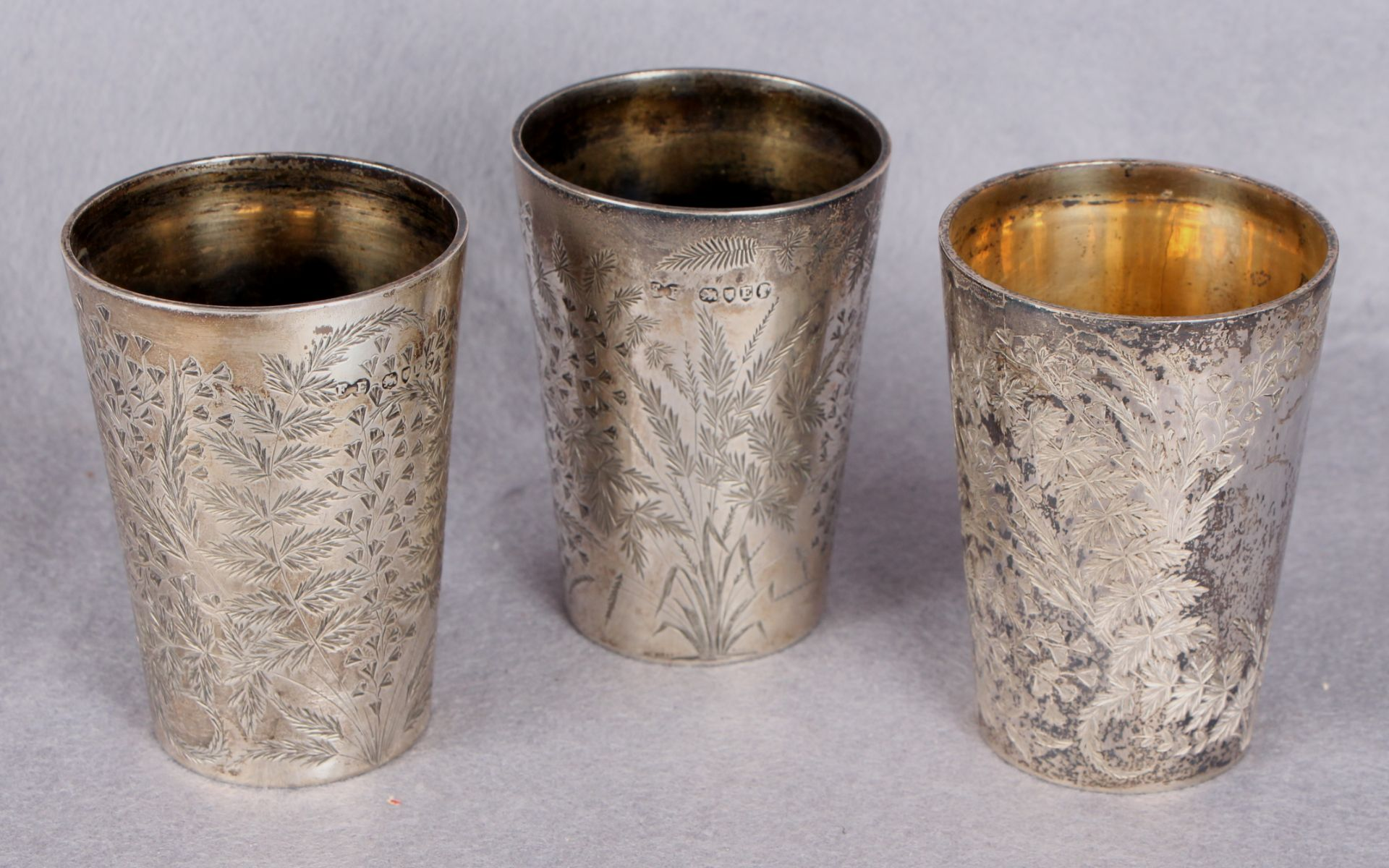 Three Victorian fern-engraved silver beakers of tapering circular form,