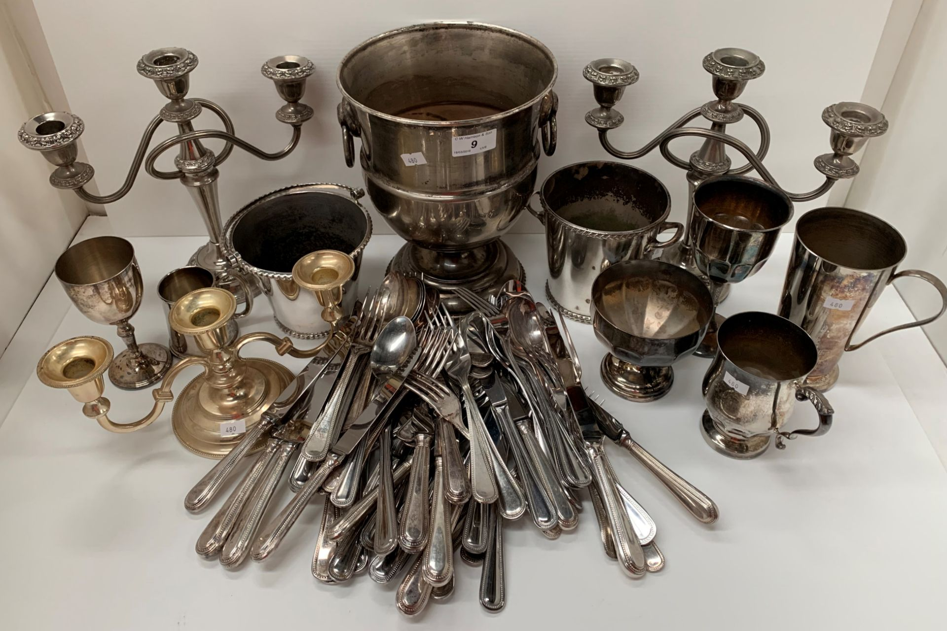 Lot 9 - A plated two handled champagne bucket, two plated candelabras, plated table cutlery, mug, etc.