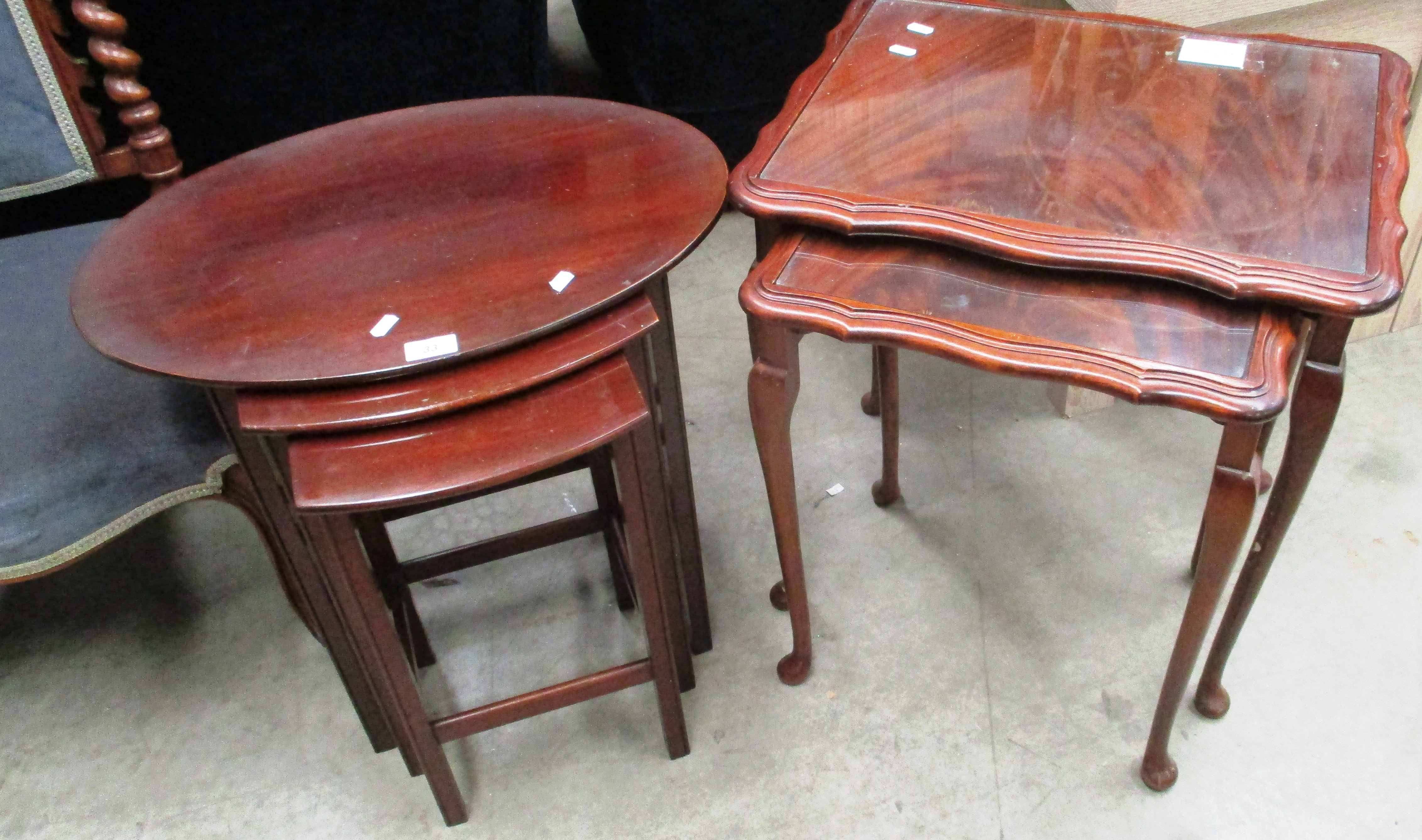 Lot 33 - A nest of 3 mahogany coffee tables and a nest of 2 walnut coffee tables with glass tops (2)