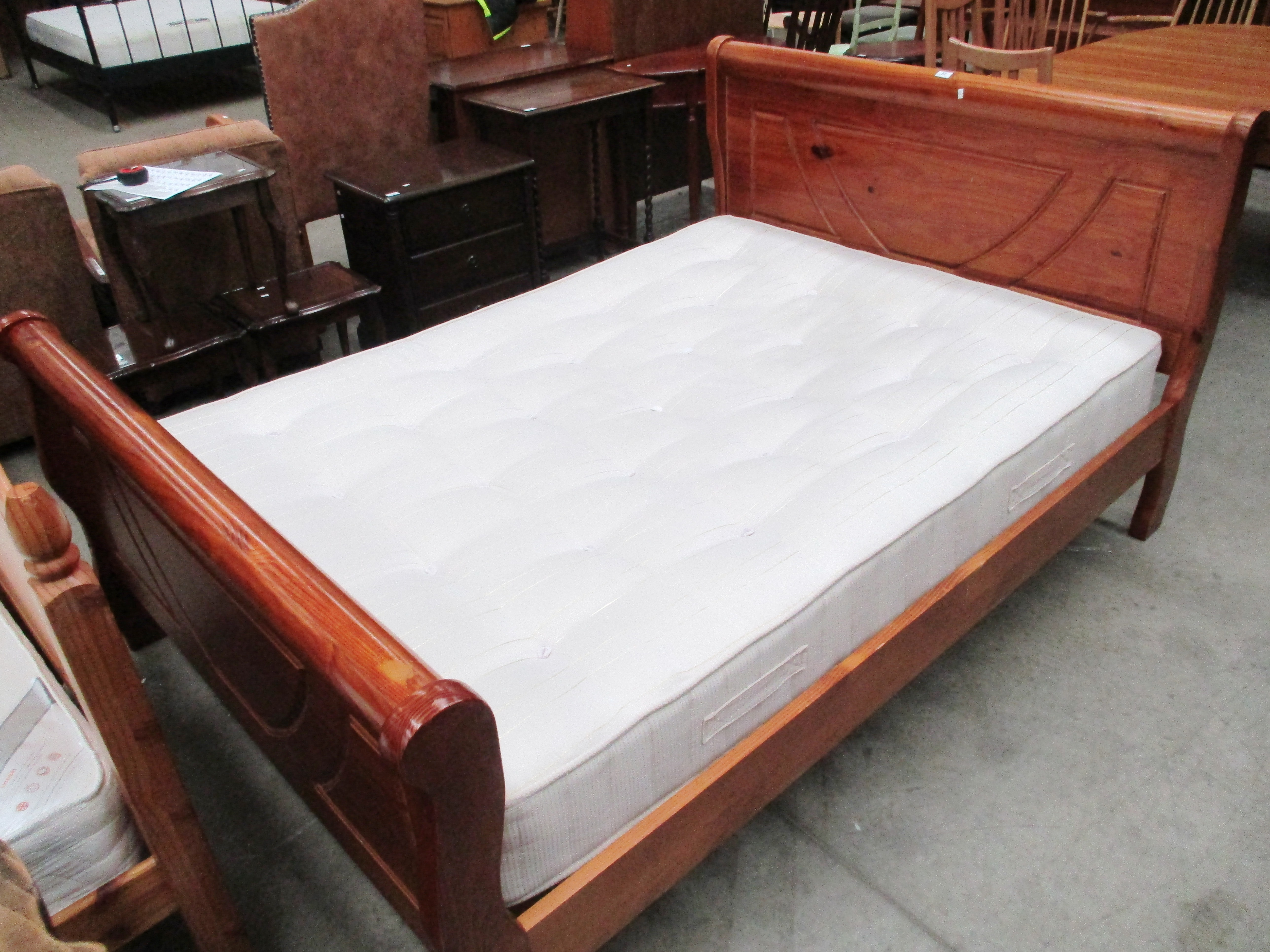 "Lot 23 - A pine framed 4'6"" sleigh bed with a Dreams Fortune orthopedic mattress (slight marking to one"