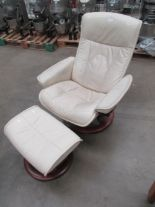Lot 25 - An Ekornes beige leather upholstered swivel recliner armchair and matching footstool