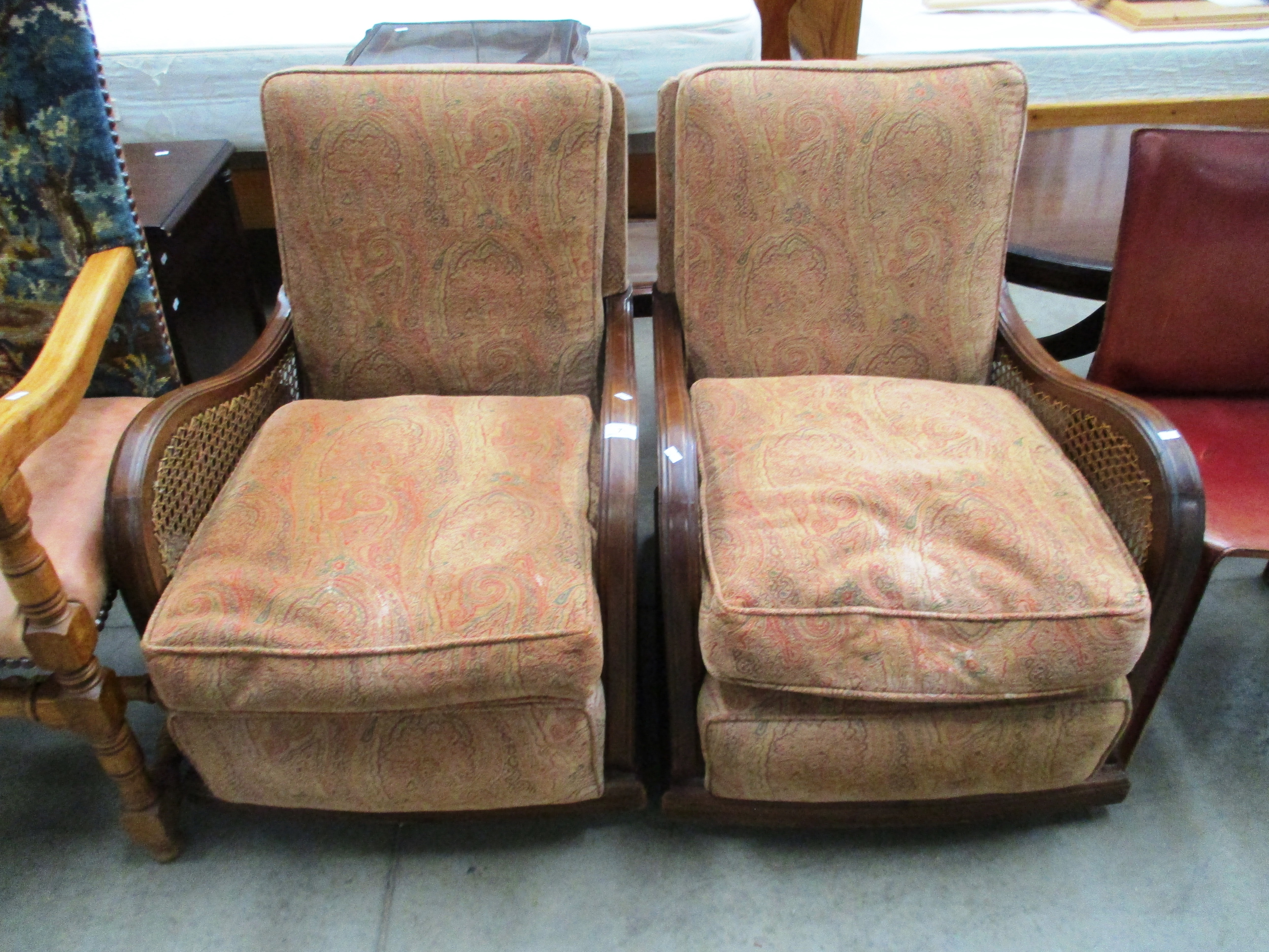 Lot 7 - A pair of mahogany framed easy armchairs with woven sides and brown patterned upholstered seat