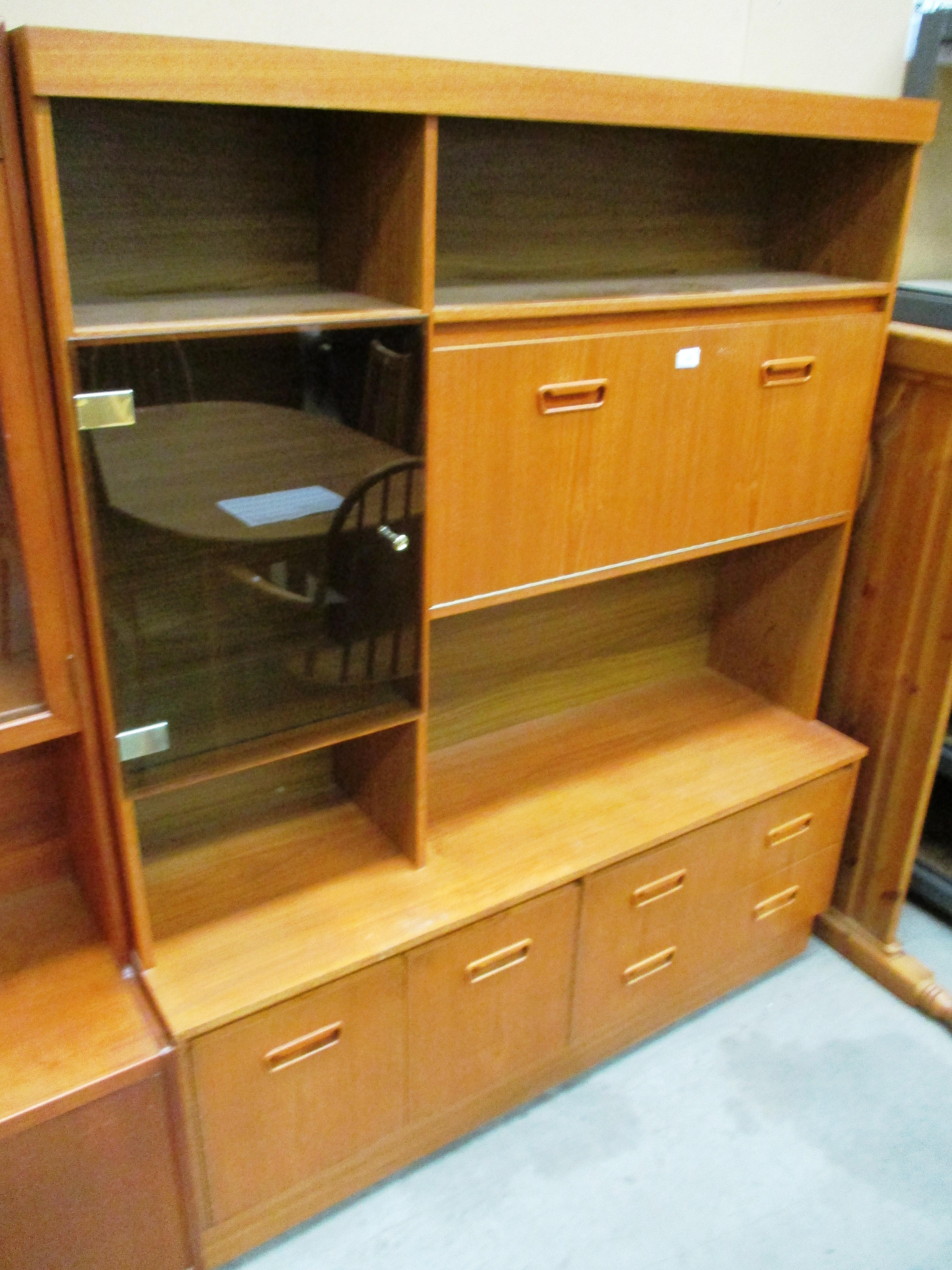 Lot 19 - A teak wall unit with 3 upper doors (1 smoked glass glazed) over 2 drawers 2 door base 136 x 168cm