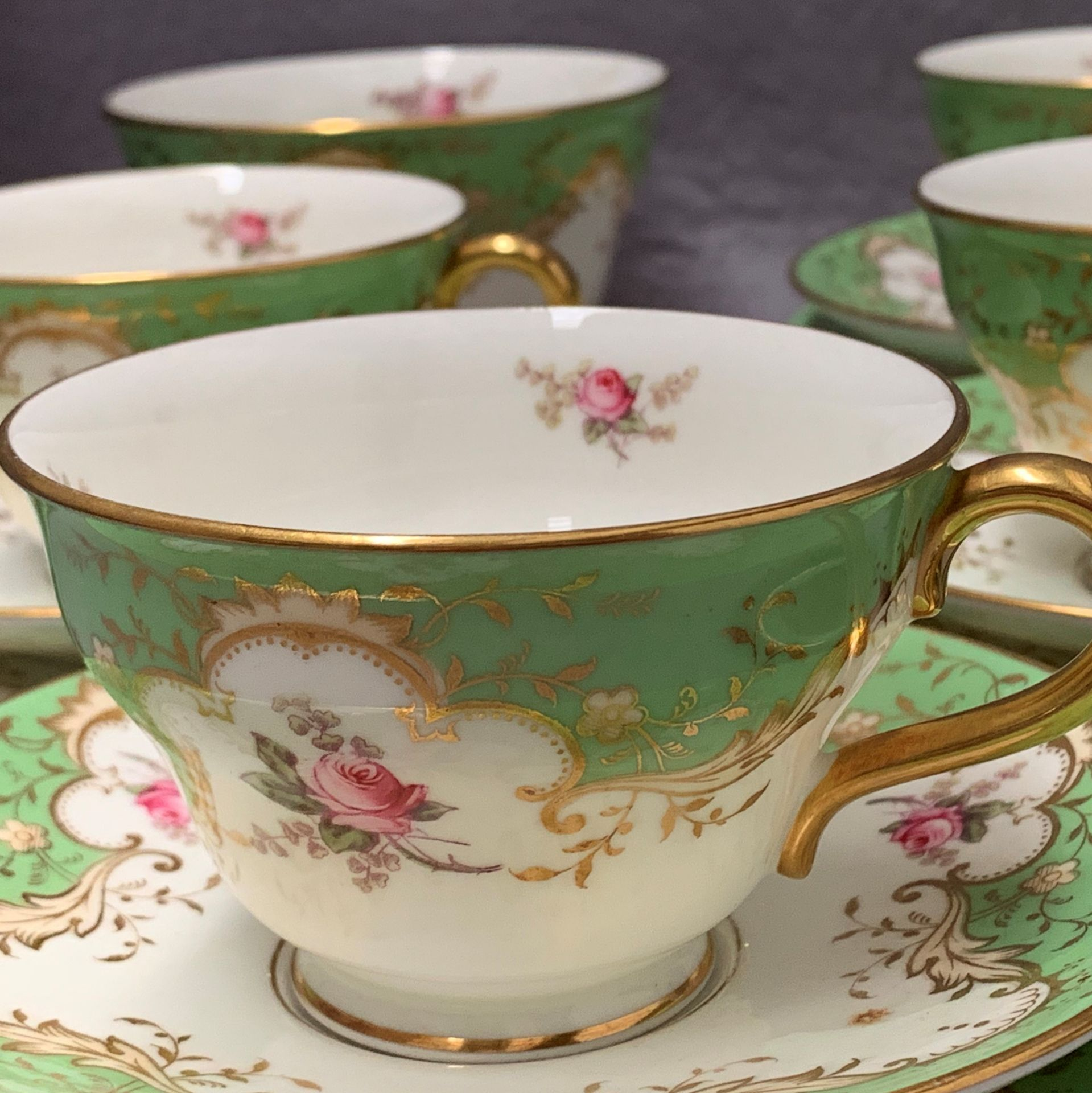 Lot 42 - Coalport, for Harrods, tea set in green and gilt with rose motif, five cups and six saucers,