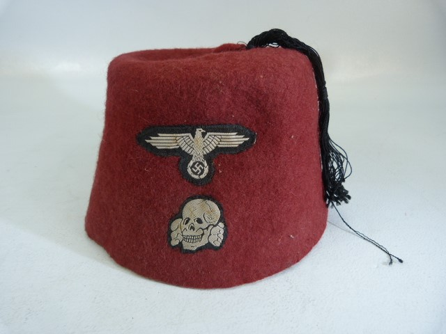 Lot 36 - WWII German SS volunteers Red dress cap with central black tassel with woven eagle and totenkopf