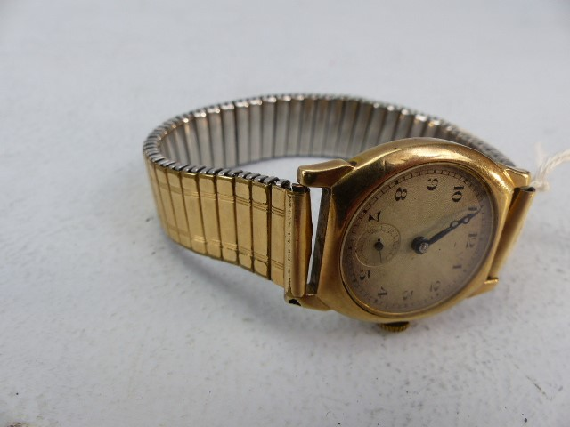 Lot 23 - A 9CT GOLD EARLY 20TH CENTURY GENTS WRISTWATCH, gold and cream dial, cushion shaped Stolkace case,