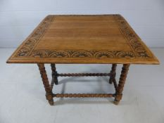 Stripped oak drop leaf table with poker work design