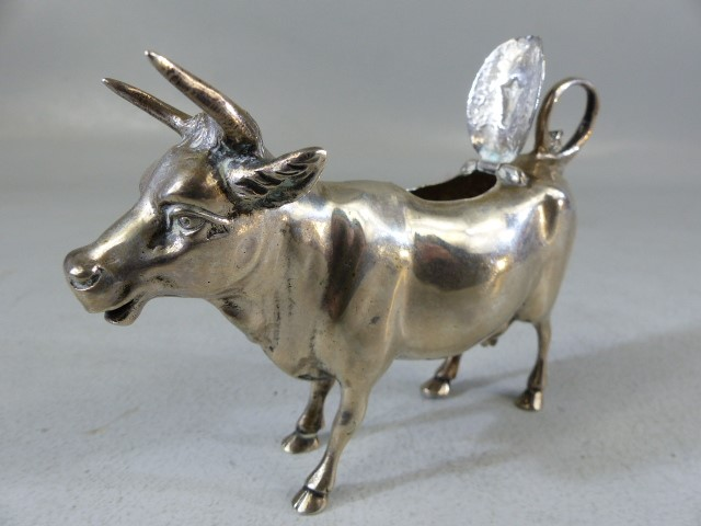 Lot 5 - Silver Continental hallmarked 'Cow' creamer. Marked 800 to belly. The hinged lid with floral motif