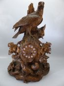 Large Black Forest heavily carved clock decorated with birds, with central clock face with enamel