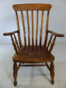 A Victorian kitchen Windsor chair, with a shaped rail over swept bars, flanked by scrolled arms over