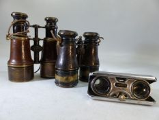 Three sets of binoculars, two leather-bound