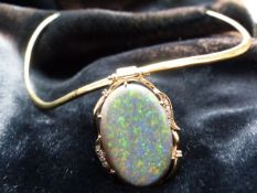 Single Collet pendant with a wavy frame edge of yell swags, set with an oval cabochon cut Opal and