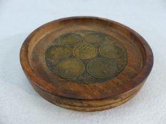 Seven Nazi coins set into a small wooden tray