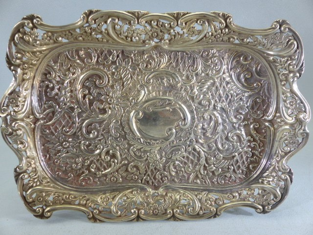 Lot 9 - Silver coloured Repousse style tray with hallmarked silver topped bottles one clear one red labelled