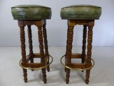 Pair of bar stools with green leather upholstery and brass foot rail