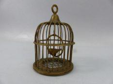 Brass bird in a cage on swinging hoop